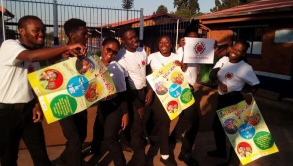 City Year South Africa service leaders smiling holding posters at a school