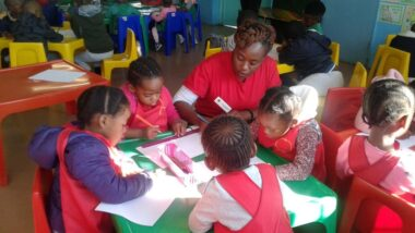 City Year South Africa serving leader working with a table of learners in school