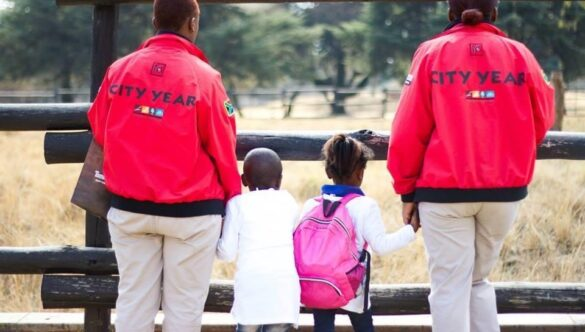 Two City Year service leaders holding hands with learners on a field trip to an animal reserve
