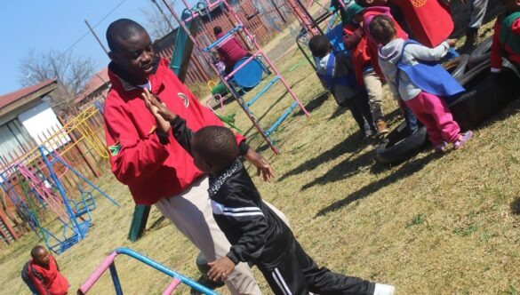 Service leader on the playground high-fiving a learner