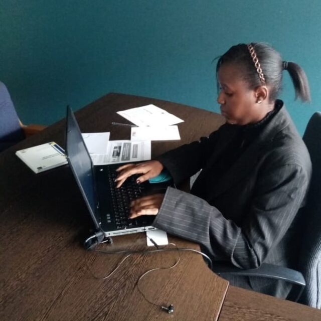 Female service leader using the computer in an office and wearing a suit